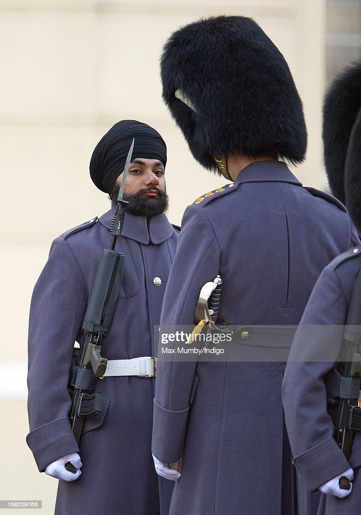 Sikh Guardsman Jatenderpal Singh Bhullar (L), a soldier in the Scots Guards, forms up with his fellow soldiers on the parade ground of Wellington Barracks before going on guard duty in the forecourt of Buckingham Palace on December 11, 2012 in London, England. Guardsman Bhullar is the first Sikh Guardsman to wear a turban rather than the traditional bearskin whilst on guard duty.