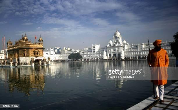 Sikh holyman walks near the sacred pond of Golden Temple on the occasion of birth anniversary of Guru Nanak in Amritsar India November 28 2012
