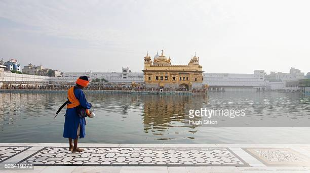 sikh man by pool at golden temple - hugh sitton india stock pictures, royalty-free photos & images