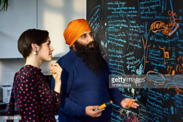sikh man explaining ideas to colleague by blackboard - entrepreneur stock pictures, royalty-free photos & images