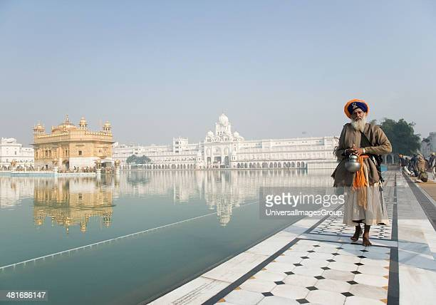 Sikh man in traditional clothing standing near a pond with a temple in the background Golden Temple Amritsar Punjab India