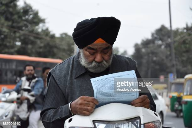 Sikh man reads the timeline of Babri Mosque demolition case during the black day on the 25th anniversary of Babri Mosque demolition in New Delhi...