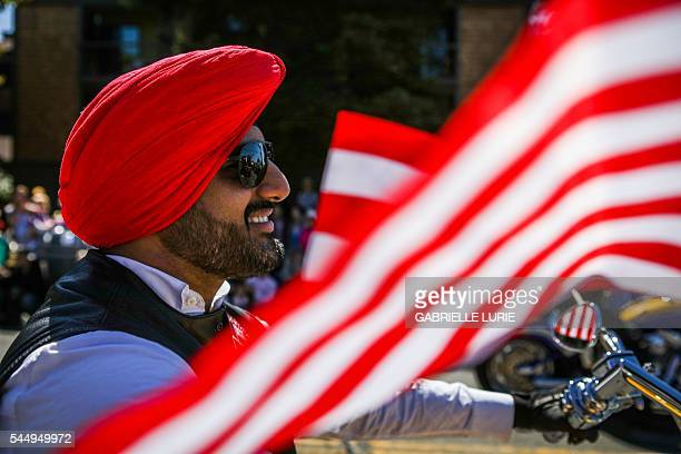 A Sikh man rides on a motorcycle with the 'Sikh Riders of America' group during the 4th of July Parade in Alameda California on Monday July 4 2016 /...