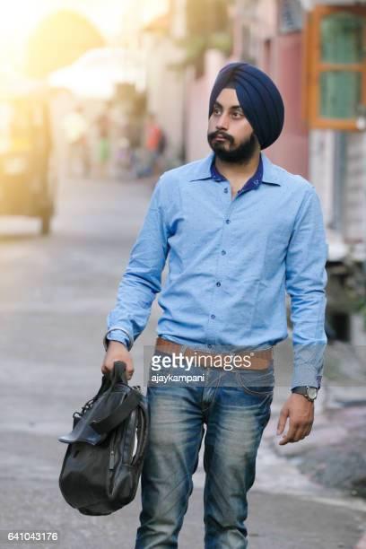 Sikh man standing outdoors with bag