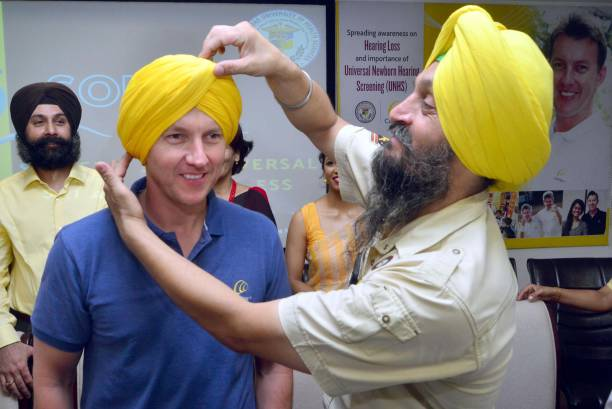 Sikh man tying turban to Former Australian Cricketer and Cochlear`s Global Hearing Ambassador Brett Lee during the awareness about the Universal...
