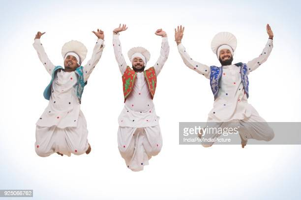 sikh men jumping in the air - lohri festival stock pictures, royalty-free photos & images