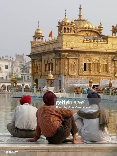 sikh men sitting on the marble floor looking at the darbar sahib (golden temple) in amritsar, punjab, india - victor ovies fotografías e imágenes de stock