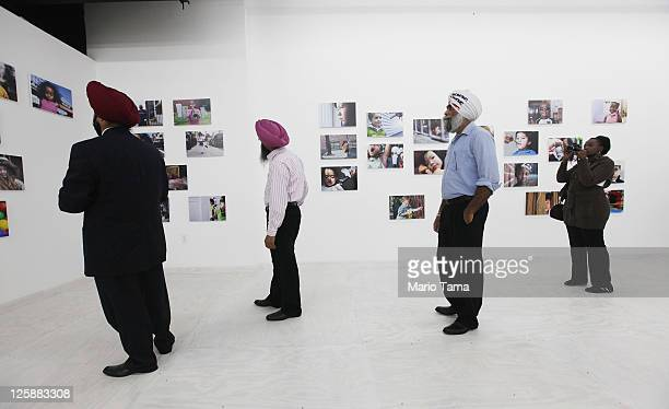Sikh men view the opening exhibition of photographer Danny Goldfield's 'NYChildren' project at the grand opening of the Park51 community center and...