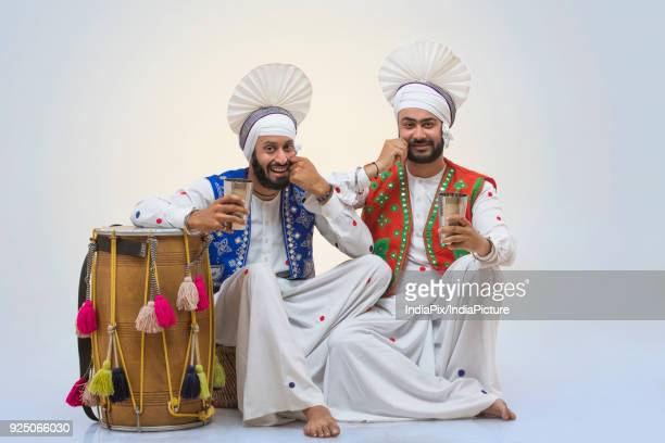 sikh people drinking lassi during baisakhi celebrations - lohri festival stock pictures, royalty-free photos & images