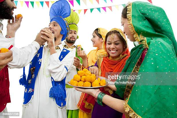 Sikh people eating laddoos