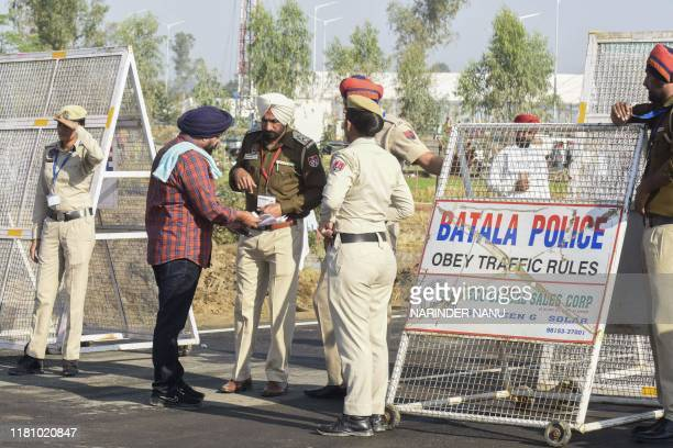 A Sikh pilgrim shows his documents to police before crossing over to Pakistan for the inauguration ceremony of the Kartarpur Corridor in Dera Baba...