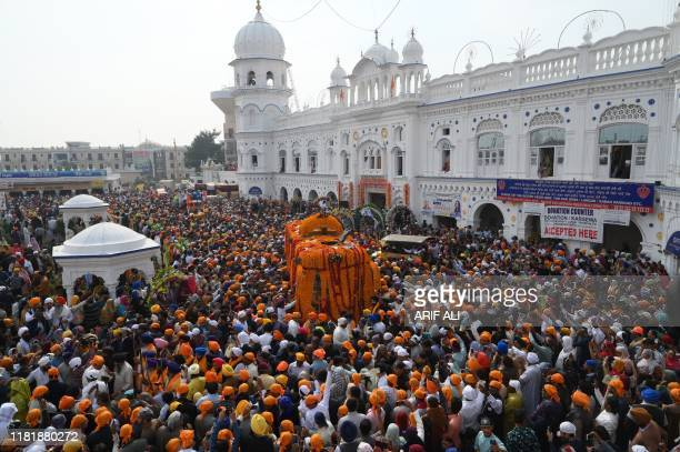 Sikh pilgrims gather around the Palki Sahib on the 550th birth anniversary of Guru Nanak Dev at Nankana Sahib a Pakistani city about 80 kilometres...