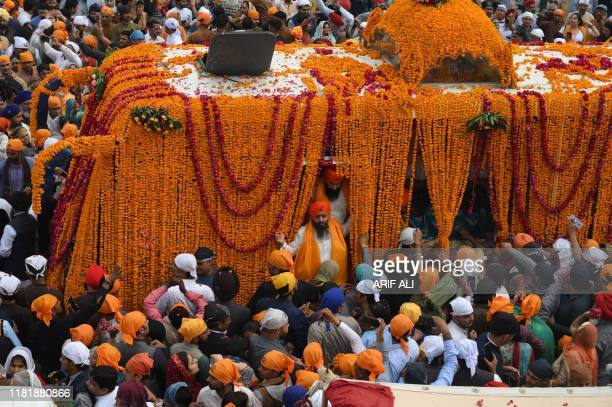Sikh pilgrims gather around the Palki Sahib on the 550th birth anniversary of Guru Nanak Dev at Nankana Sahib a Pakistani city about 80 kilometres...