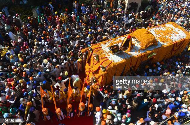 TOPSHOT Sikh Pilgrims gather around the Palki Sahib on the occasion of the 549th birth anniversary of Guru Nanak Dev in Nankana Sahib a district in...
