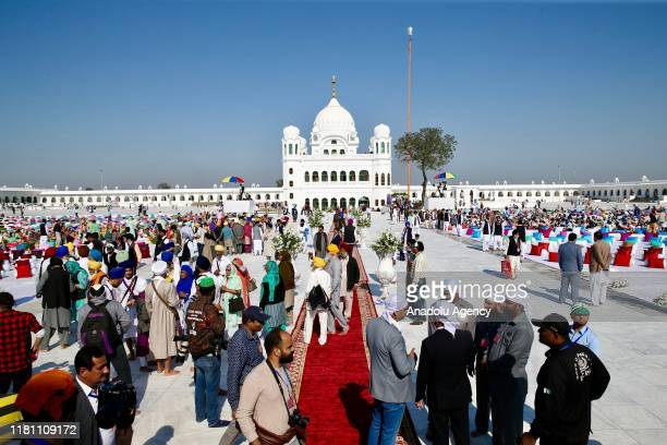 Sikh pilgrims gather to offer prayers towards the Temple of Baba Guru Nanak Dev at Gurdwara Darbar Sahib during the inauguration ceremony in...