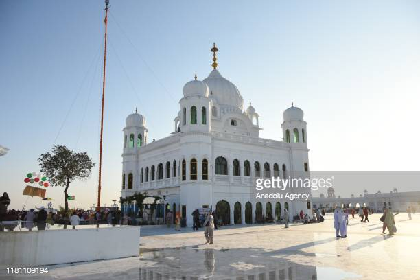 Sikh pilgrims gather to offer prayers towards the Temple of Baba Guru Nanak Dev at Gurdwara Darbar Sahib during the inauguration ceremony in...