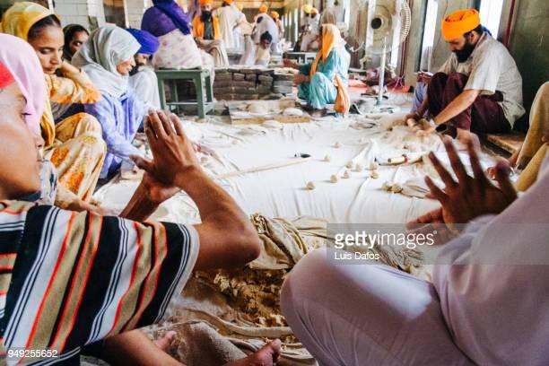 Sikh pilgrims preparing food in the Langar community kitchen of the Golden Temple