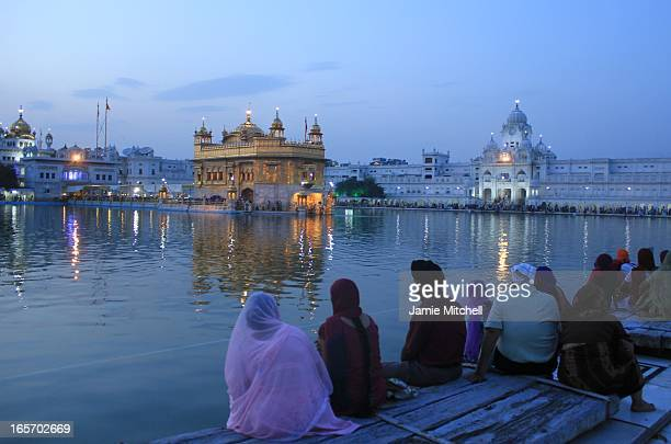 CONTENT] Sikh pilgrims sitting by the calm waters surrounding the holy Harmandir Sahib during day's last light in the city of Amritsar Punjab India
