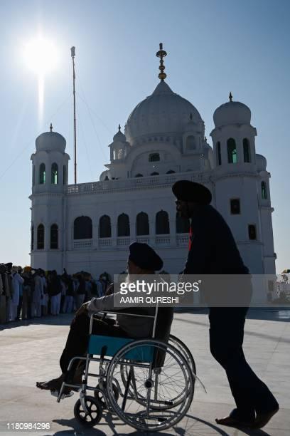Sikh pilgrims stand in a queue to visit the Shrine of Baba Guru Nanak Dev at Gurdwara Darbar Sahib in Kartarpur near the Indian border on November 9...