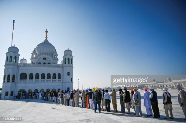 TOPSHOT Sikh pilgrims stand in a queue to visit the Shrine of Baba Guru Nanak Dev at Gurdwara Darbar Sahib in Kartarpur near the Indian border on...