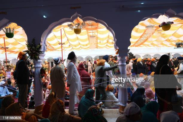 Sikh pilgrims take part in a religious ritual as they gather to celebrate the 550th birth anniversary of Guru Nanak Dev at Nankana Sahib a Pakistani...