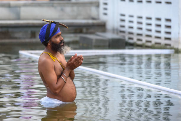 Sikh praying and celebrating holi bath at Golden Temple pool. Kirpan should always be carried according to sikh tradition