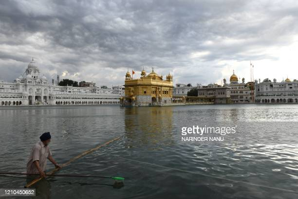 A Sikh Sewadar cleans the holy sarovar as dark clouds are seen above the Golden Temple during a governmentimposed nationwide lockdown as a preventive...