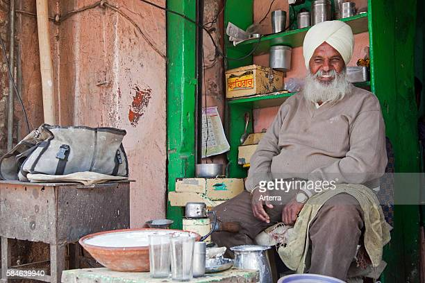 Sikh shopkeeper wearing turban selling lassi traditional yogurtbased drink in Jaipur Rajasthan India