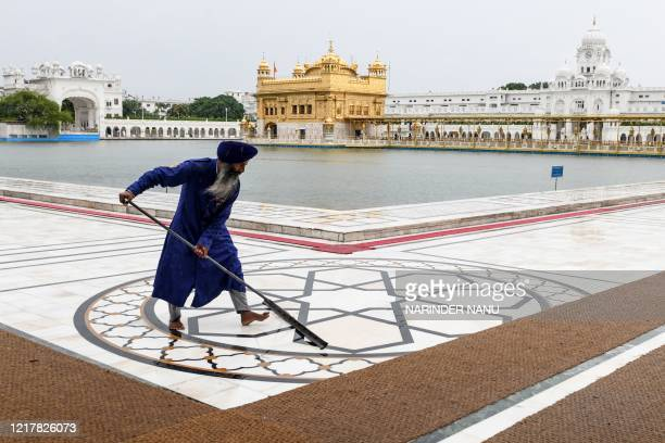 Sikh volunteer cleans the floor after heavy rain on the occasion of the 36th anniversary of Operation Blue Star at the Golden Temple in Amritsar on...