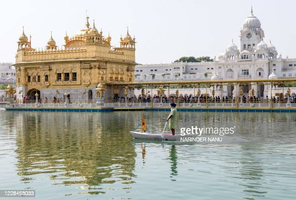 Sikh volunteer cleans the holy sarovar as devotees pay respect on the occasion of the 481th death anniversary of Baba Guru Nanak Dev Ji -- the...