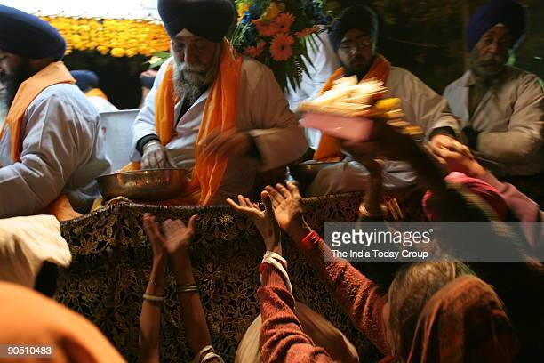 Sikh volunteers distribute prasad near gurudwaras Gol market on the occasion of Guru Govind Singh's birth anniversary gurupurb New Delhi