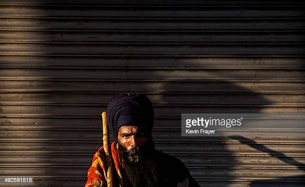 Sikh warrior or Nihang who often guard Gurdwaras or temples sits in the street as another man sleeps on May 21 2014 in Delhi India India elected...