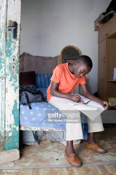 Sikhumbuzo Hlahleni age 15 a student at Cape Town City Ballet's youth company does his geography homework in his family house on March 15 2010 in...