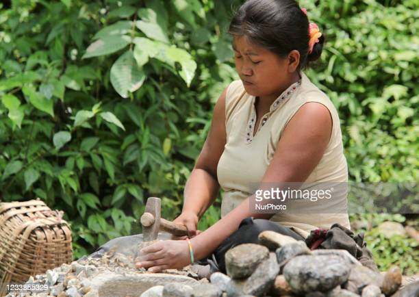 Sikkimese woman laborer breaks rocks into smaller stones which will be used in making cement and building construction materials in Khechuperi,...