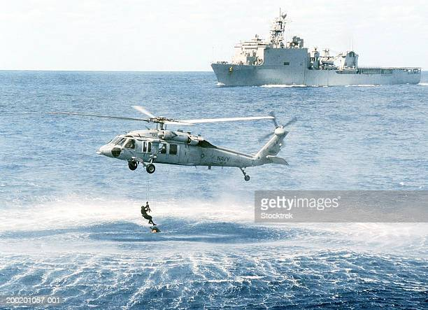 sikorsky mh-60s knighthawk retrieving soldier from atlantic ocean - navy ship stock pictures, royalty-free photos & images