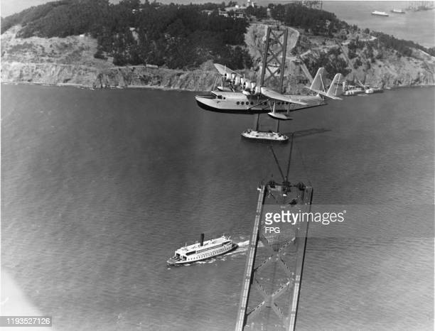 A Sikorsky S42 flying boat of Pan American Airways over San Francisco Bay during construction of the San FranciscoOakland Bay Bridge California 1935