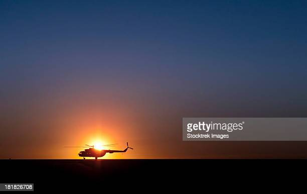 A Sikorsky S-61L Mk II helicopter taxis on the runway during sunrise.