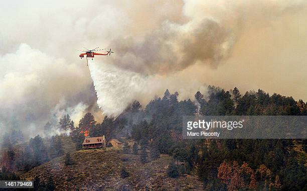 Sikorsky S64 Aircrane firefighting helicopter drops water on a hotspot burning close to homes near Horsetooth Reservoir June 11 2012 near Laporte...