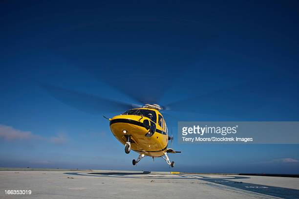 a sikorsky s-76 utility helicopter taking off from the helipad on an oil rig. - helicopter photos stock pictures, royalty-free photos & images
