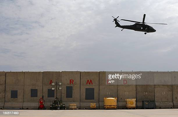 Sikorsky UH 60 Black Hawk helicopter flies by a wall reading 'Armed' at the Kabul International airport in Kabul on August 18 2012 France is the...