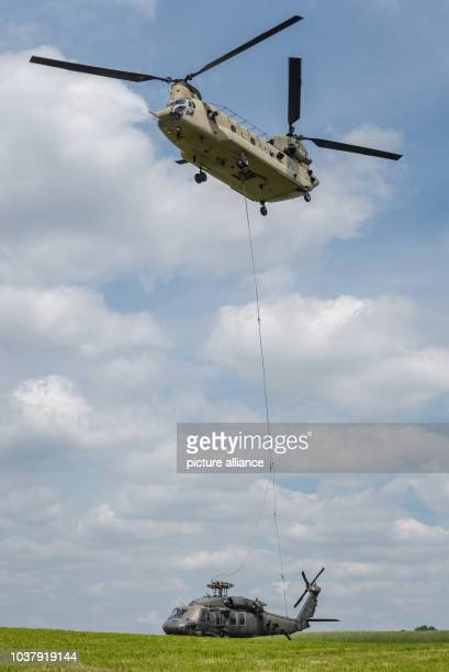 A Sikorsky UH60 Black Hawk helicopter is being hauled out by a Boeing CH47 Chinook helicopter in Plankenfels Germany 18 May 2015 The pilots had to...