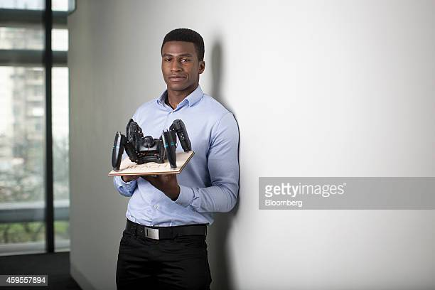 Silas Adekunle founder of Reach Robotics holds one of the company's smartphone controlled Berserker gaming robots as he poses for a photograph...