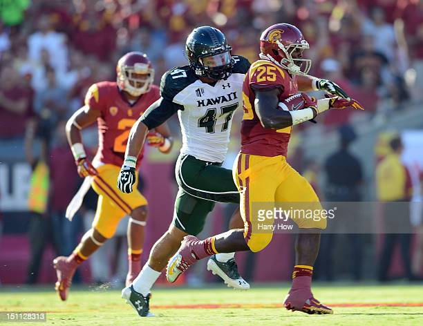 Silas Redd of the USC Trojans rushes as he is chased by Kamalani Alo of the Hawaii Warriors during the first quarter at Los Angeles Coliseum on...