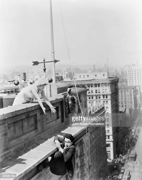 Silent comic Harold Lloyd clings to the parapet of a skyscraper in a hairraising scene from 'Feet First' directed by Clyde Bruckman