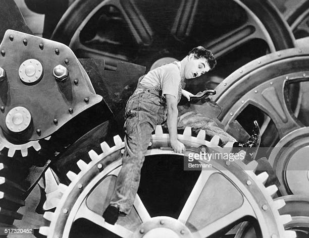Silent film comedian Charlie Chaplin exagerates movements and actions sitting on gears in the motion picture Modern Times in 1936