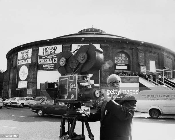 Silent film star Harold Lloyd operates a 3strip technicolour separation camera outside the Camden Roundhouse in London at a press preview of 'Cinema...
