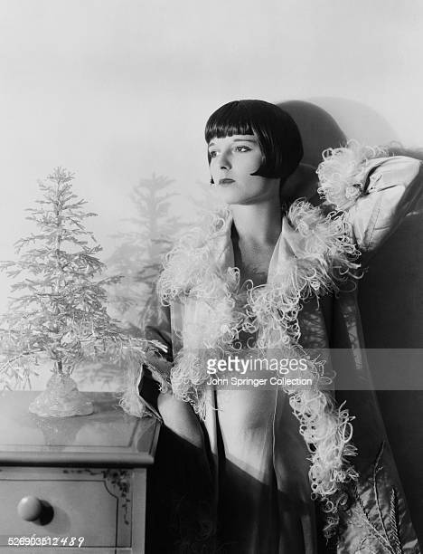 Silent film star Louise Brooks standing 3/4 length next to a small decorative tree Photograph circa 1920s