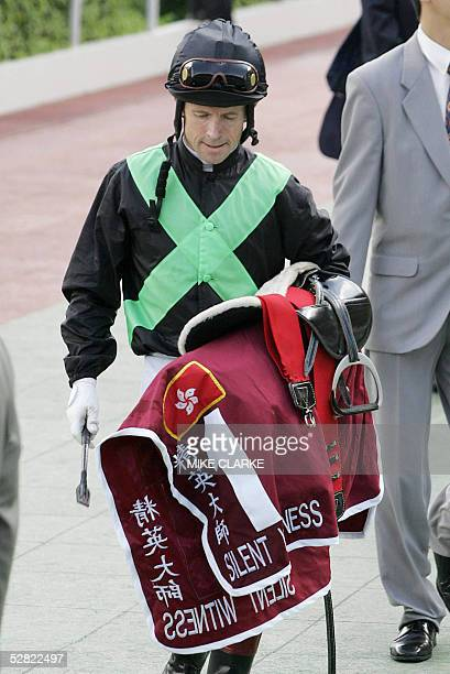 Silent Witness jockey Felix Coetzee looks down after losing in the Champions Mile race at the Shatin racetrack in the New Territories district of...