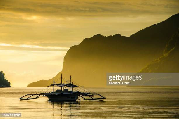 Silhouete of Outrigger at sunset in El Nido, Bacuit Archipelago, Palawan, Philippines