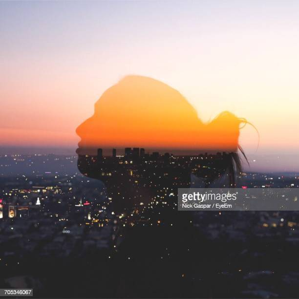 silhouette against cityscape during sunset - left eye stock photos and pictures